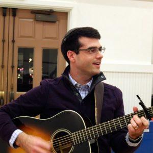 Photo of Rabbi Aaron Miller playing the guitar at Metro Minyan